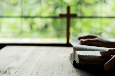 Croix qui s'ouvrent au-dessus de la Bible sur une table en bois avec éclairage de fenêtre
