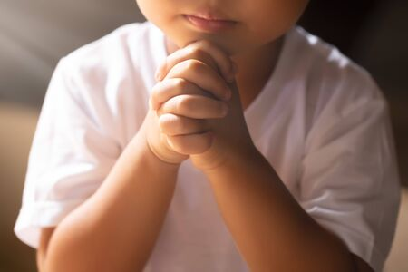Asian boy praying in the morning with hands held together
