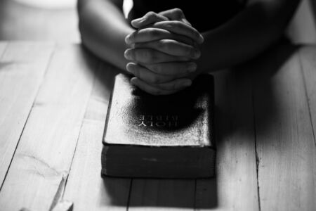 Praying hands of teens on old bible over wooden table background