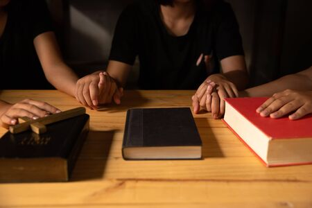 Christian people prays together around wooden table with bible.