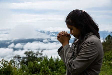 Christian worship in forest, Happy teen deep breath fresh air on top mountain breathing clean air. Girl enjoying nature and praying to god.