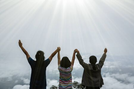 Christian worship with raised hand in forest, Happy teens deep breath fresh air on top mountain breathing clean air. Girls enjoying nature and praying to god.