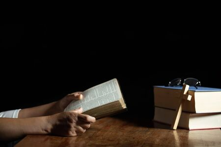 Christian women read the scriptures in the house with two books with a cross on the side of the book placed on the table. 스톡 콘텐츠