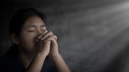 Girl while praying for christian religion with blurred of her body background, Casual woman praying with her hands Standard-Bild