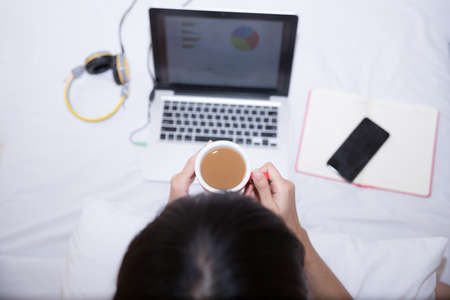 Young woman drinking coffee at home in her bed and checking her laptop, top view Reklamní fotografie