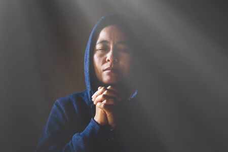 Woman Pray for god blessing to wishing have a better life. begging for forgiveness and believe in goodness. Christian life crisis prayer to god.