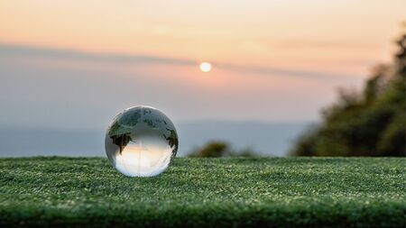 Crystal ball transparent in grass with beautiful sunset color. beautiful still life with glass ball. landscape with glass sphere. copy space