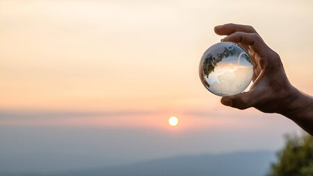 Crystal ball photography - sunset mountain, hand holding the ball