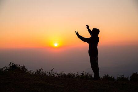 Silhouet van de mens die bidt in het zonsopgangconcept voor religie, aanbidding, gebed en lof.