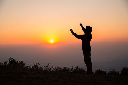 Siluetta dell'uomo che prega nel concetto di alba per religione, adorazione, preghiera e lode.