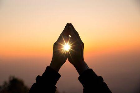 Silueta de la mano del hombre cristiano rezando, espiritualidad y religión, hombre rezando a Dios. Concepto de cristianismo. Foto de archivo