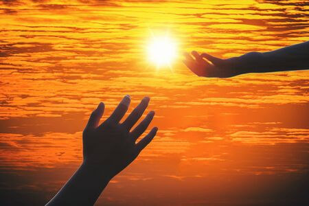 Giving a helping hand on the background of the sunset. Silhouette of helping hand concept and international day of peace. Imagens