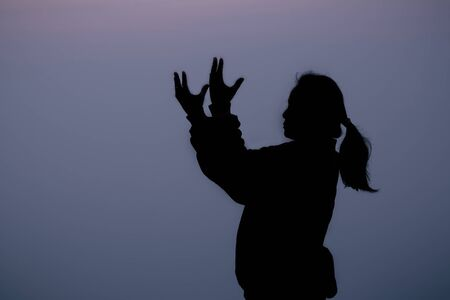 Silhouette of woman standing with arms raised on mountain and praying over beautiful sunrise background