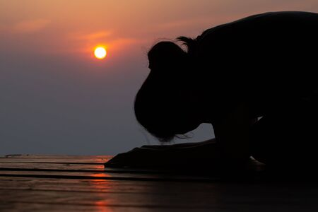 Silhouette of woman praying in the morning over beautiful sunrise background