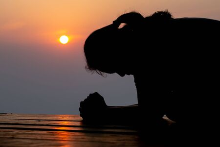 Silhouette of woman praying in the morning over beautiful sunrise background Imagens