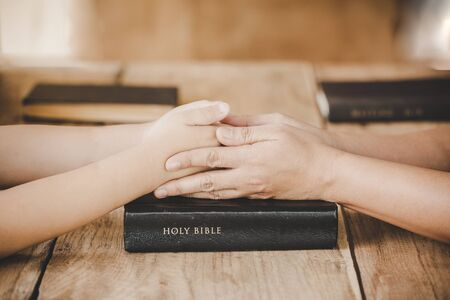 Couple mother and son are holding hands and pray together on wooden table with the light from side with copy space for your text