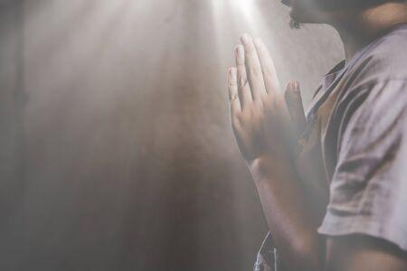 Praying asian teen girl hoping for better. Asking God for good luck, success, forgiveness. Power of religion, belief, worship. Holding hands in prayer.
