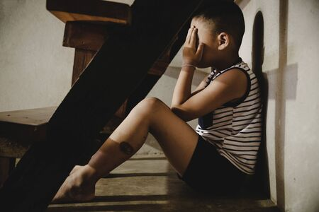 Neglected lonely child, Young boy sitting on the floor with Copy Space.