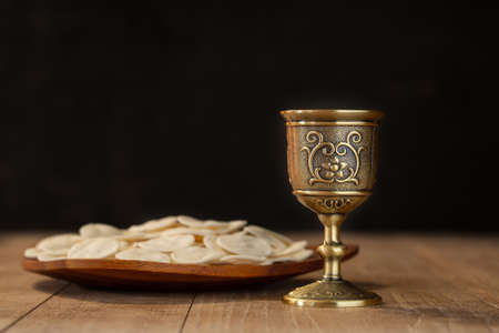 Pray with holding loaf and little cup of the wine. adult and faithful in Jesus Christ woman in a holy communion.