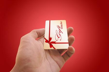 dar un regalo: Man s mano que sostiene una tarjeta de vale de regalo