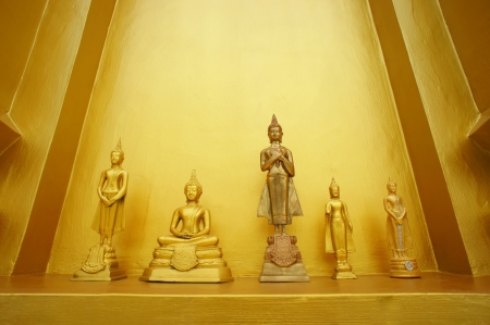 Small golden buddha statues with golden background photo