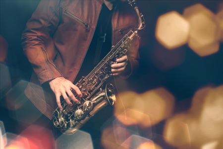 ステージ上でパフォーマンスのジャズ サックス奏者。カラー フィルターと六角形のボケ味追加。