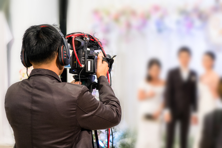 professional videographer recording wedding ceremony day with professional camcoder and boardcasting. Foto de archivo