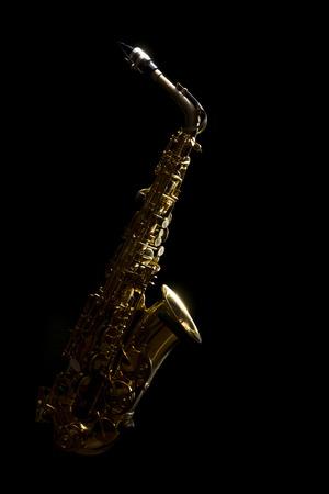 saxophone alto discret et lumière dans le fond sombre Banque d'images