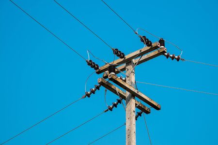 against the current: electrical post by the local road with power line cables in bright and clear blue sky.