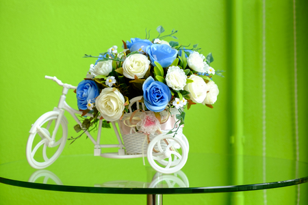artificial flowers in the tricycle pot over glass table in the coffee cafe