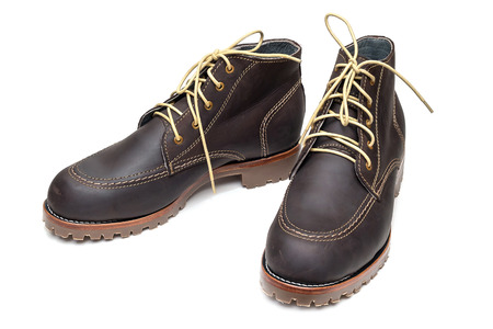 new pair of dark brown color full grain nubuck leather boots with thick anti-slip rubber sole on isolated white background.