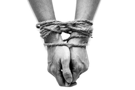 enslaved: victim, slave, prosoner male hands tied by big rope isolated on the white background. People have no freedom concept image.