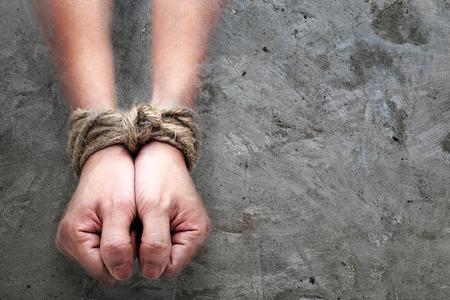 被害者、奴隷、アズカバン コンクリート背景に大きなロープによって結ばれた男性の手。いくつかの悪いことをスレーブまたは常習の人々 の概念イ 写真素材