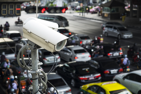 secure: Traffic security camera (CCTV) working on the traffic jam in the work day morning. Recording technology of on road traffic and protection from crime in the city. Stock Photo