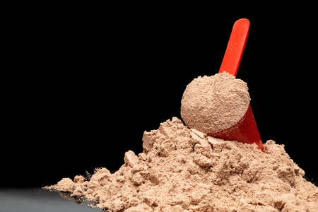 Close-up Whey Protein Powder in measuring scoop. Bodybuilding Nutrition Supplements with a copy space.