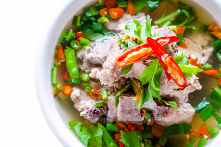 Close up Spicy Pork with Pork bone Soup on the isolated white background. Leng soup in Thai word.