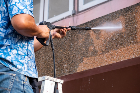 Man using High Power Pressure Water for Smash Cleaning Dirty Wall outdoor.