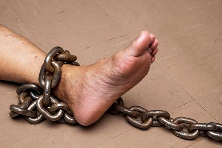 Servidumbre de cadena de prisionero masculino en el suelo, concepto de violencia y criminal.
