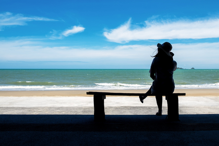 Silhouette Picture of a Woman Relaxing on the Wood Bench Near the Beach.