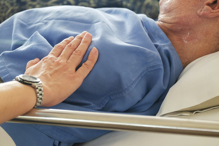 Woman Touched and Praying For Sick Old Man in the Hospital. Stock Photo
