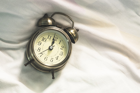 Very Late on Twelve, Classsic Style Alarm Clock on the Bed Ater Late Awake.