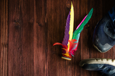 Shuttle Cock Kicking, Colorful Feather Chinese Jianzi Foot Sports, Hacky Sack Foot Feather on Wood Background.