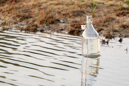 A Glass Water Bottle Floating in the Lake. 写真素材 - 120548438