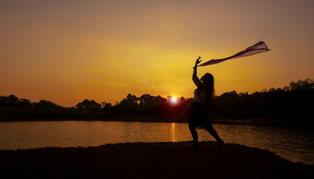 Silhouettes Picture of Girl Worship Jesus with Flag Dance in the Sunset at the River. Flare Added.
