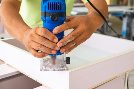 Asian Man Building Furniture with Router doing Edge Tape Trimming. 스톡 콘텐츠