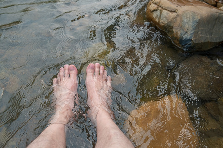 Man Relaxing His Feet in the Cold and Fresh Waterfall. 写真素材