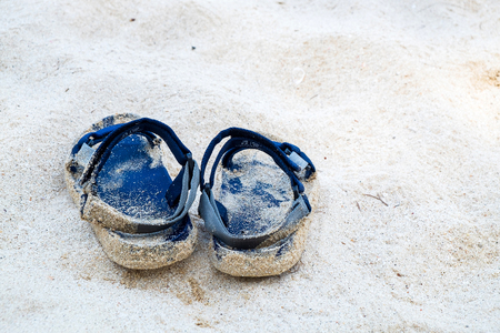 Sandals on the Sand of the Ocean Beach in the Summer with Copy Space.