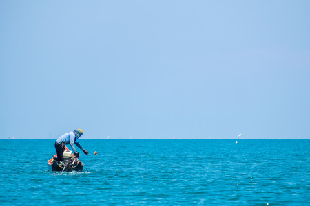 Fisherman Working in the Sea with Shell to Trap a Small Squid. 写真素材