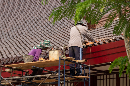 Two Male Workers are Fixing and Repairing the Damaged Roof Tiles.