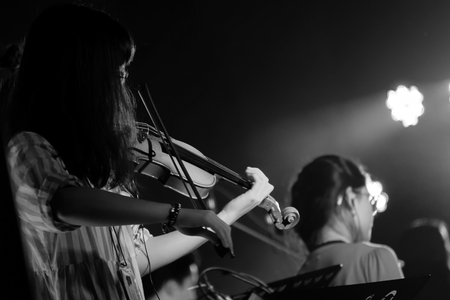 Young Violinist Girl Performance with Her Violin iNstrument on the indoor Concert Stage. Black and White.